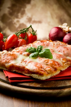 photo of delicious slice of pizza with basil leaf on it Stock Photo - 9456512
