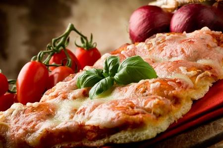 Foto van heerlijke plak van pizza met basilicum blad op het