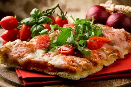 a fette di pizza con rucola e pomodorini sul tavolo in legno