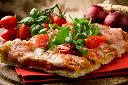 sliced pizza with arugula and cherry tomatoes on wooden table