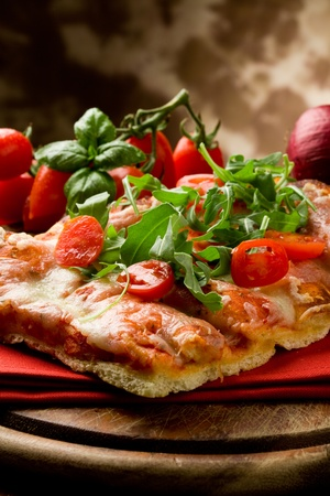 cherry tomatoes: sliced pizza with arugula and cherry tomatoes on wooden table