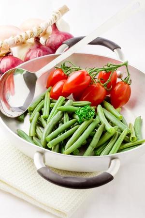 foto de alubias dentro de una olla con tomates cherry