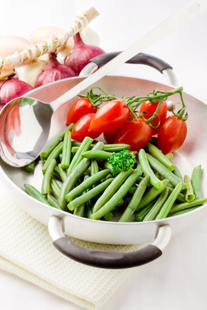 photo of french beans inside a pan with cherry tomatoes photo