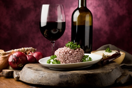 risotto: photo of delicious risotto with red wine on wooden table