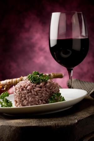 photo of delicious risotto with red wine on wooden table  photo