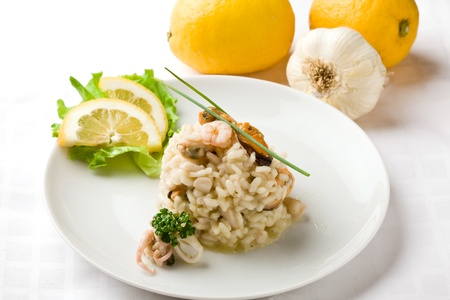 photo of delicious risotto with seafood on white isolated background photo