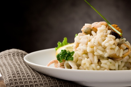 photo of delicious risotto with seafood and parsley on it