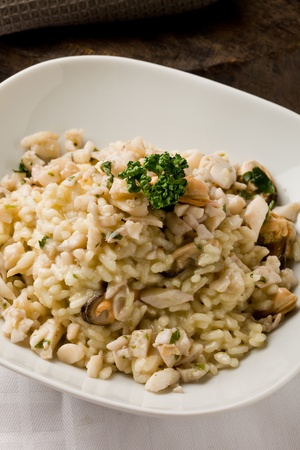 photo of delicious risotto with seafood and parsley on it  photo