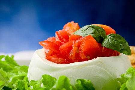 stuffed buffalo mozzarella with tomatoes and basil on lettuce over blue background photo