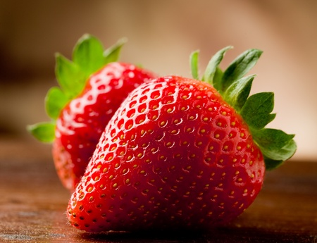 strawberry: photo of delicious strawberries on wooden table in front of brown rustical background