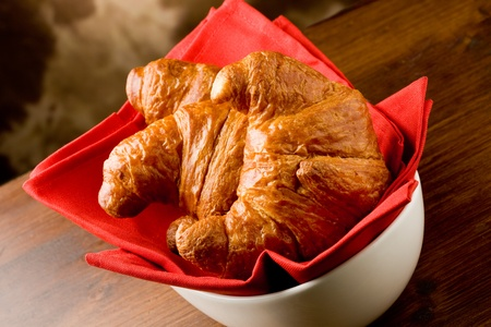 photo of delicious warm and fresh croissants on wooden table