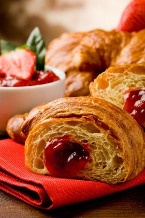 croissants: delicious golden croissants filled with strawberry marmelade Stock Photo