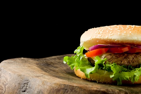 photo of delicious american hamburg on wooden table, isolated on black Stock Photo