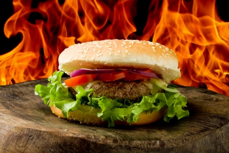 photo of delicious american hamburg on wooden table in front of a flame background Stock Photo