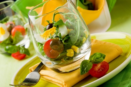 Delicious starter of mixed salad inside a glass on green wooden table photo