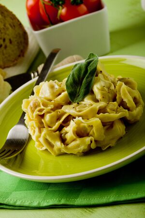delicious italian fresh tortellini with butter and sage on green wooden table  Stock Photo - 9512759