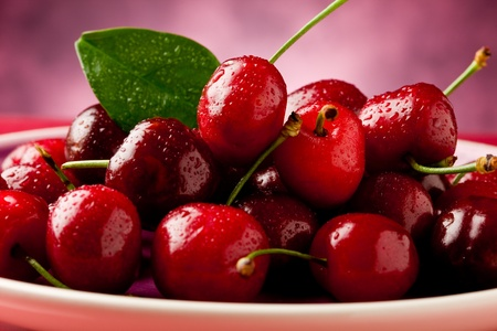 fruit drop: photo of delicious fresh cherries inside a plate on red reflecting table Stock Photo