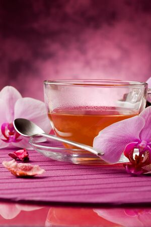 tea hot drink: photo of orchid tea inside a glass cup with big orchid flower Stock Photo