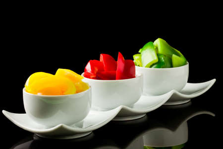 photo of colorful pepper inside three small bowls on black isolated background photo