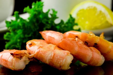 photo of grilled  king prawns on black glass table with reflection  photo