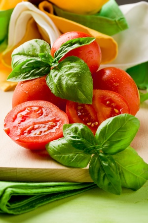 sliced cherry tomatoes with basil on wooden cutting board