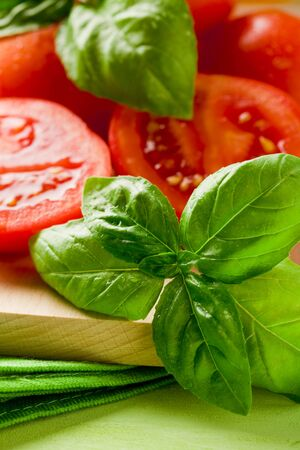 cherry tomatoes: sliced cherry tomatoes with basil on wooden cutting board