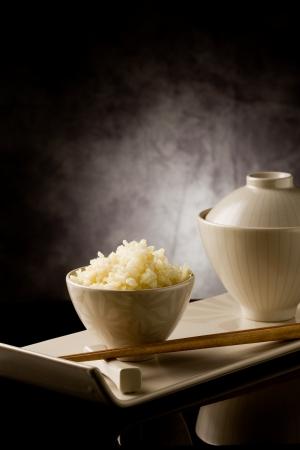 arroz chino: plato delicioso arroz asi�tico con palillos en mesa de vidrio Foto de archivo