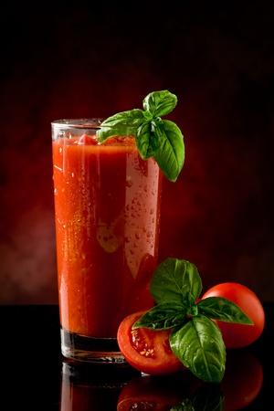 jugo de tomate: tomate delicioso bloody mary c�ctel en reflejando tabla de vidrio con luz focal
