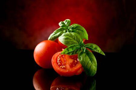 pomidory: świeże pomidory pociętego na plasterki z Bazyli na tabeli szkła z dodatkowego światła