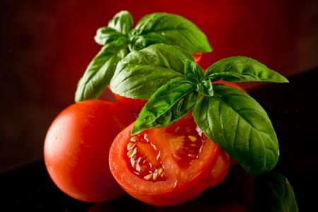 tomate: tomates fraîches tranchées au basilic sur table de verre avec de la lumière spot  Banque d'images