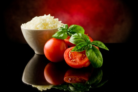 baked beans: rice inside a bowl with basil and fresh cherry tomatoes  Stock Photo