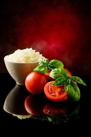 rice inside a bowl with basil and fresh cherry tomatoes  photo