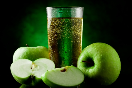 appel water: Verse sprankelende groene appelsap op groene plek verlichte achtergrond Stockfoto
