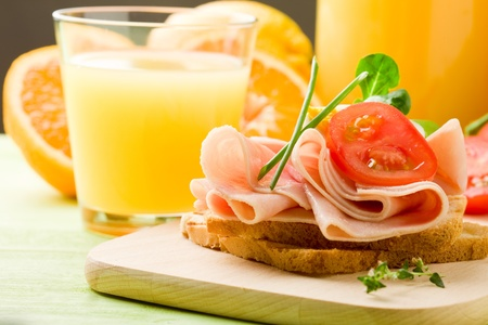 phto of delicious toast with ham on wooden table with orange juice