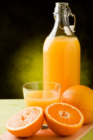 thirst quenching: fresh orange juice inside a glass on wooden table  Stock Photo