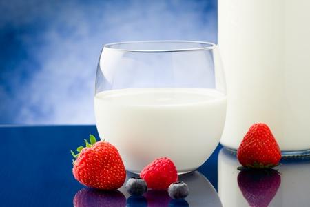 milk milk products: leche fresca en mesa de vidrio azul con bayas alrededor Foto de archivo