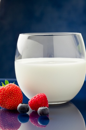 fresh milk on blue glass table with berries around photo