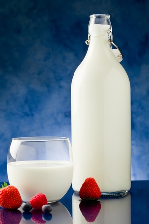 fresh milk on blue glass table with berries around Stock Photo - 9703647