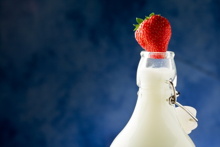 milk bottle with fresh red strawberry on it  photo