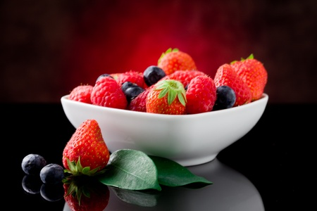 mixed fresh berries on red lighted background photo
