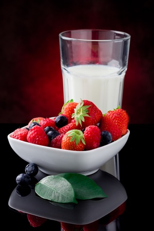 milk glass with berries on red lighted background photo