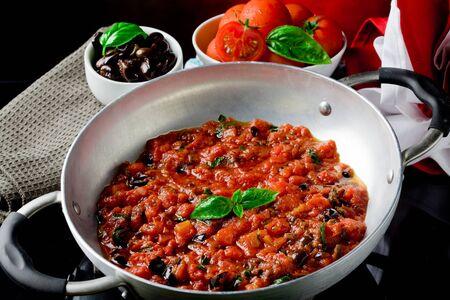salsa de tomate: salsa de tomate cocinado con aceitunas y albahaca Foto de archivo