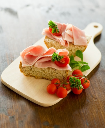snacks: delicious ham tomato sandwich with fresh parsley on wooden table with day light illumination Stock Photo