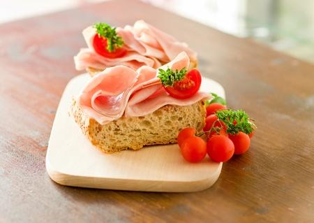 embutidos: delicicious jam�n s�ndwich de tomate con perejil fresco en la mesa de madera con iluminaci�n de luz de d�a