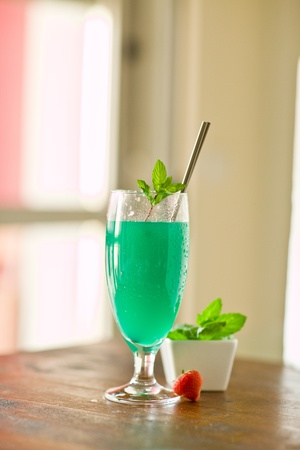 photo of delicious mint cocktail on wooden table illuminated by daylight photo