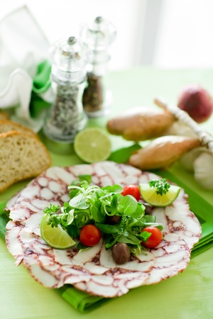 carpaccio: photo of delicious octopus carpaccio with mixed salad illuminated by daylight