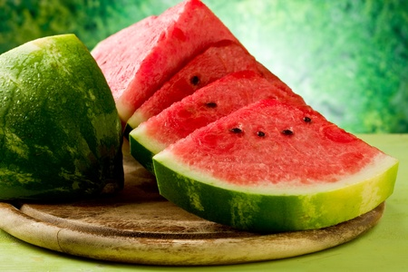 photo of fresh delicious watermelon on chopping board with green background Stock Photo