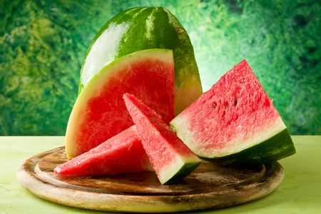 photo of fresh delicious watermelon on chopping board with green background photo