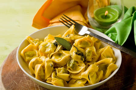tortellini: delicious italian fresh tortellini with butter and sage with green background