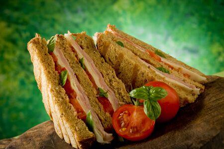 leckeren Sandwich mit Käse und Schinken auf Holztisch
